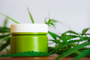 Cannabis hemp cream background with marijuana leaf - cannabis concept self care in of health care. Cosmetics with hemp extract on table. Herbal organic medicine CBD product