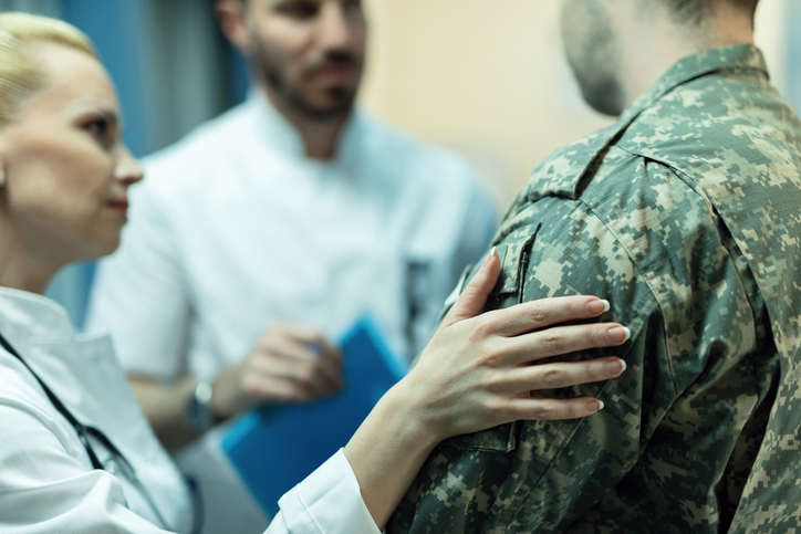 Close up of army soldier being consoled while talking with doctors at clinic.