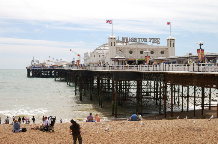 Brighton, England - July 30, 2012: People enjoying seaside on shingle beach by Brighton Pier.
