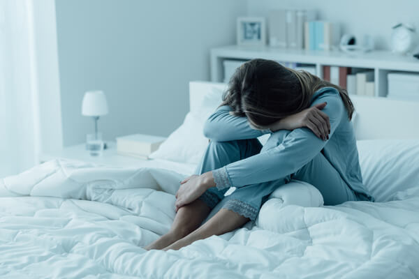 a Women with her head in her arms looking depressed on a bed