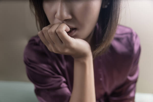 Closeup of a women chewing her nails looking anxious