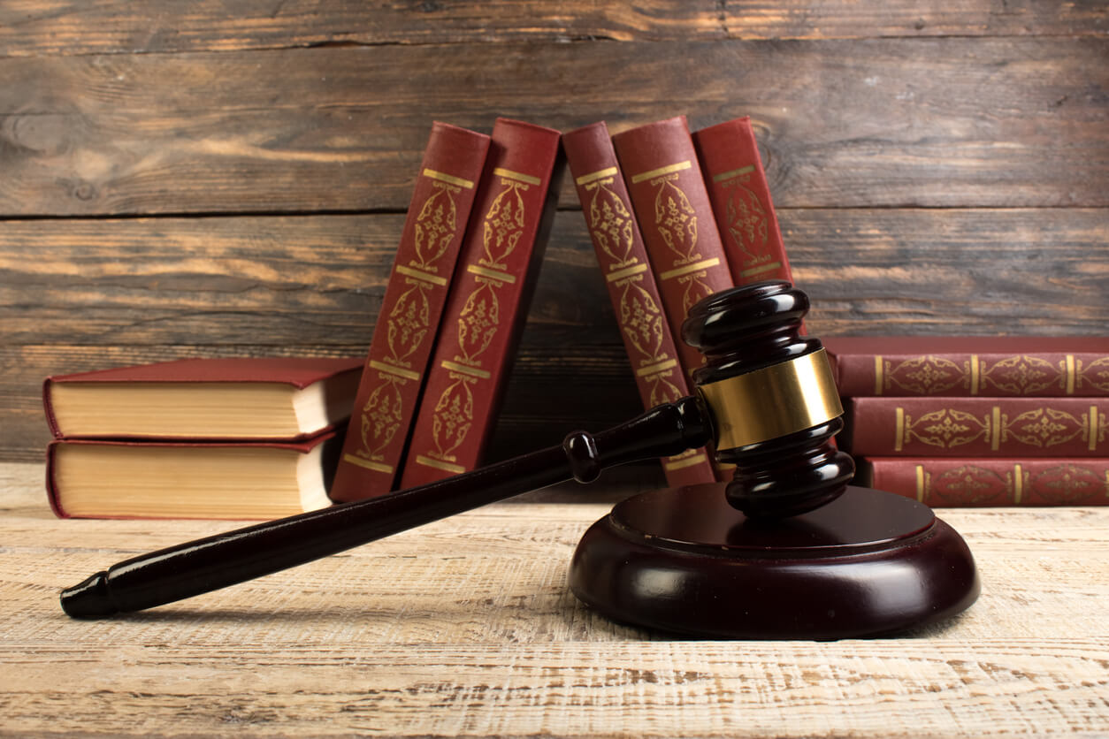 Law concept - Open law book with a wooden judges gavel on table in a courtroom or law enforcement office on the wooden background. Copy space for text