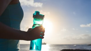 Woman holding water bottle after workout