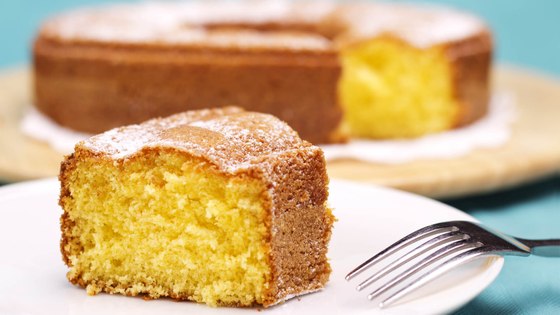 A closeup of a piece of lemon cake with icing sugar