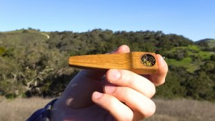 Man smoking cannabis with a wooden pipe in the open air