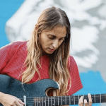 Rachel Goodrich playing guitar at an outside venue