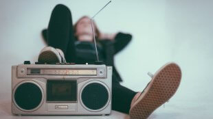 A blurry shot of a women reclining with sneakers on boombox