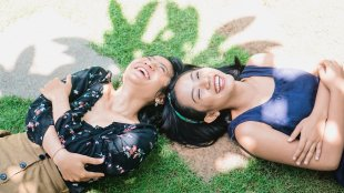 Two Girls laying down on grass smiling