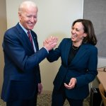 Joe Biden and Kamala Harris holding hands smiling in an office