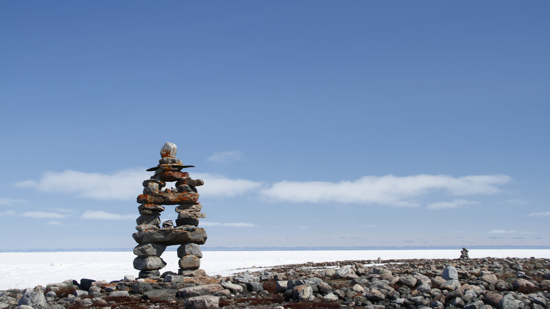 Inukshuk with frozen bay in background in Nunavut