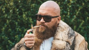 Bald and Bearded man with a fur jacket and sunglasses smoking a joint
