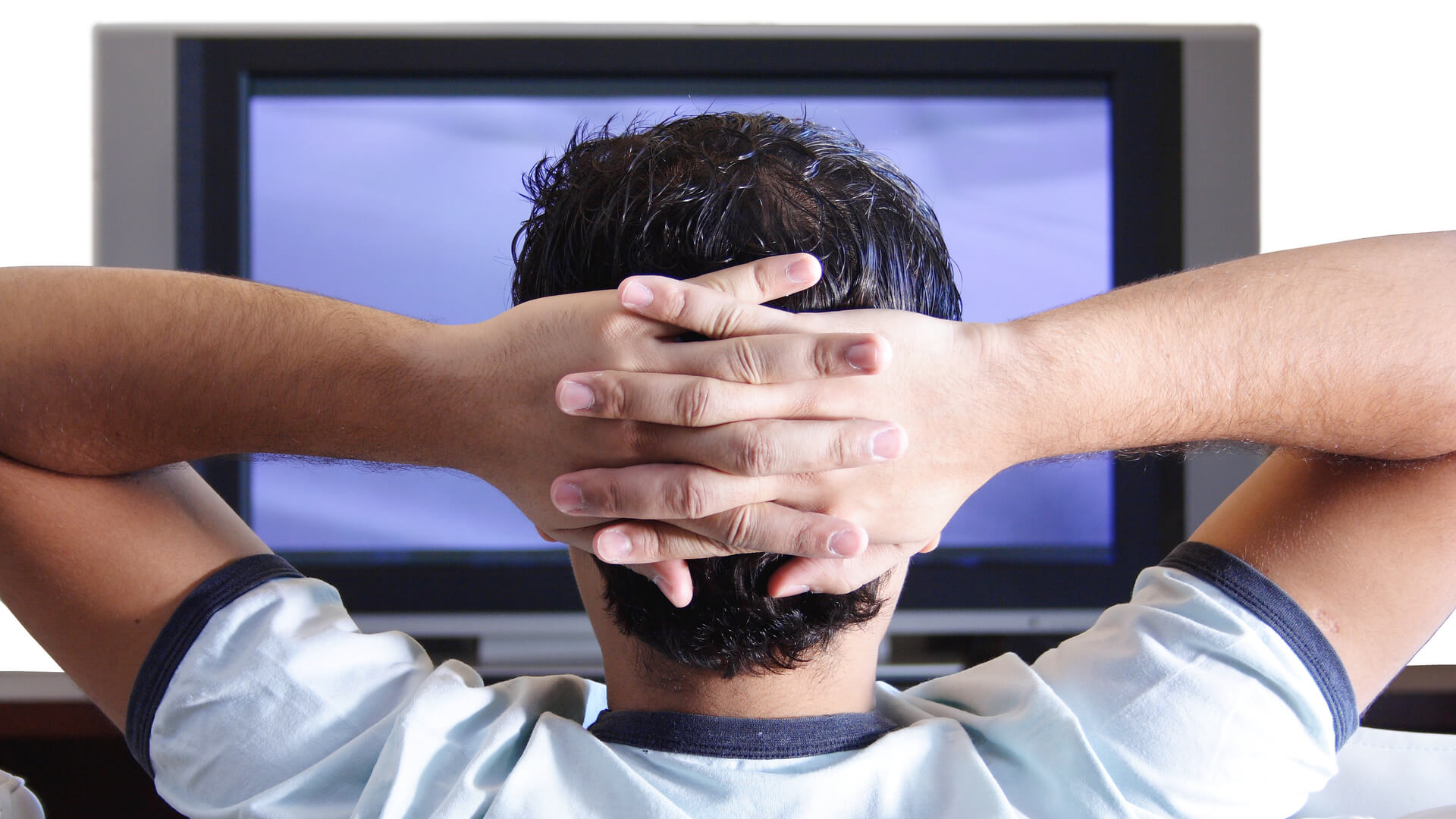 Adult sitting back with hands behind head, watching TV