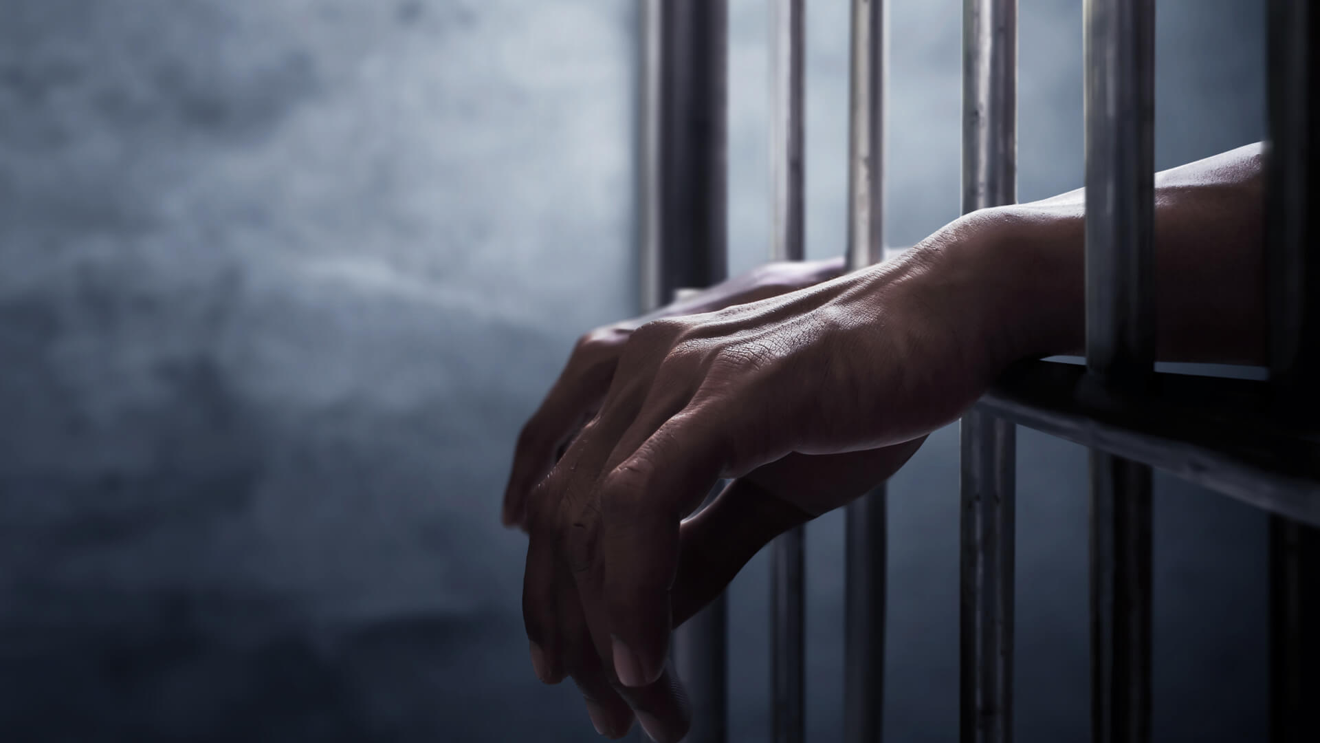 Closeup of Hand going through Prison Bars