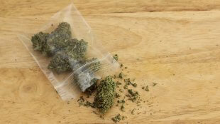 A Dime bag of weed on a wood surface