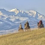 Cowboys riding on a Montana horse ranch with Mountains in the distance