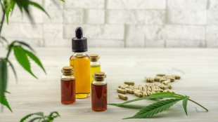 Several bottles and pills of Whole Spectrum Extract next to a hemp leaf