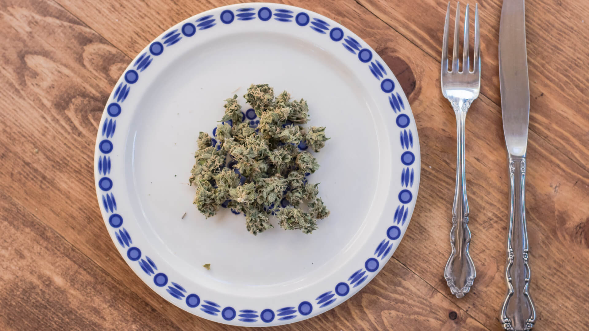 cannabis buds on a plate next to a fork and knife