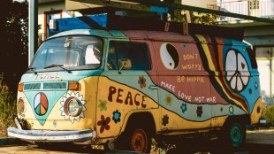 An old hippie van covered in colorful art