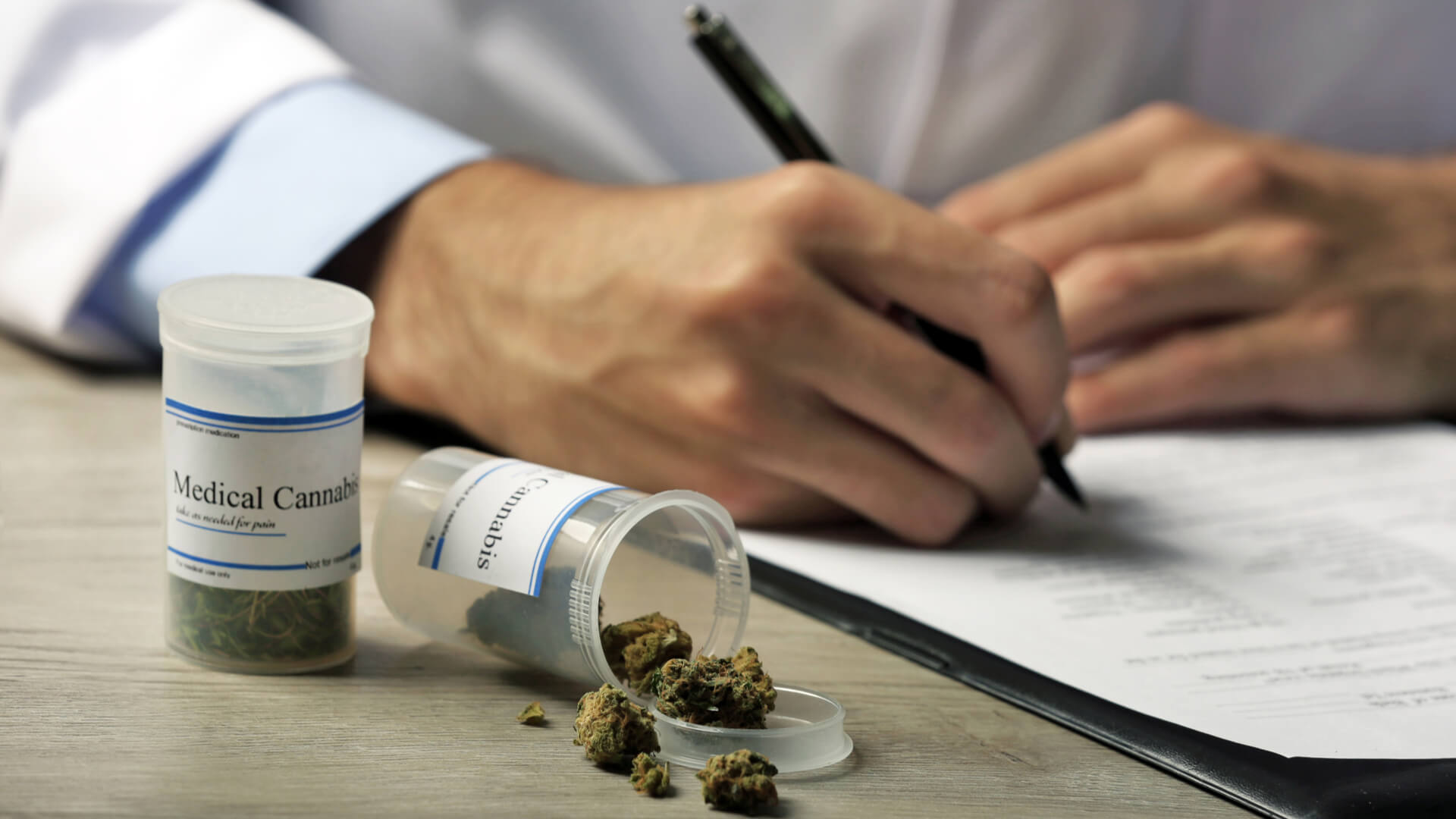 Doctor writing on prescription blank with a bottle of medical cannabis next to him