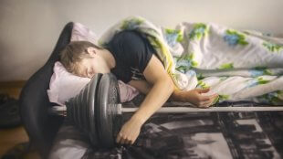 A bodybuilder guy sleeps with his athletic barbell after workout.