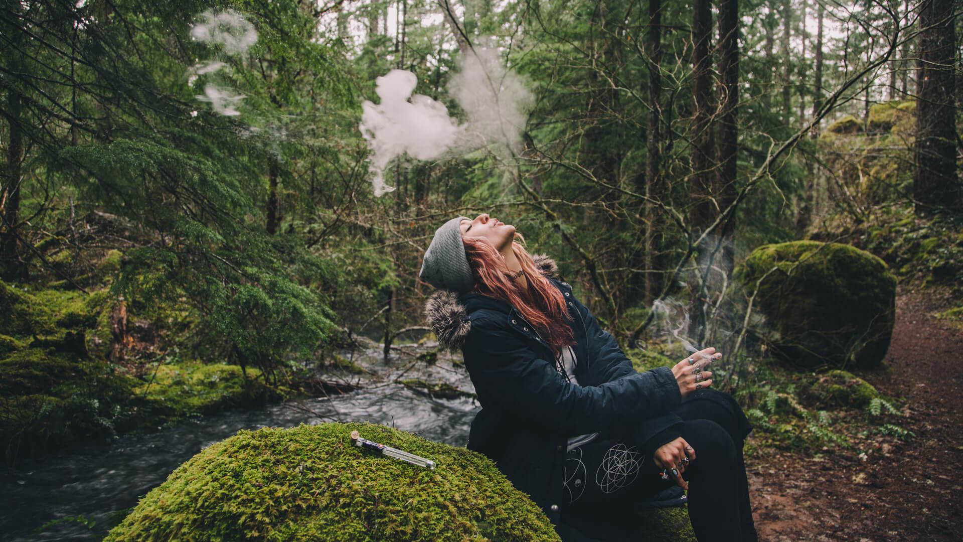 Blonde woman smoking cannabis while hiking in the woods