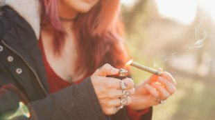 A woman lighting a joint