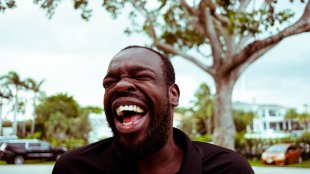 A portrait of a black man laughing on a sunny day