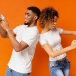 a man and women playing a video game on cellphones on a orange background