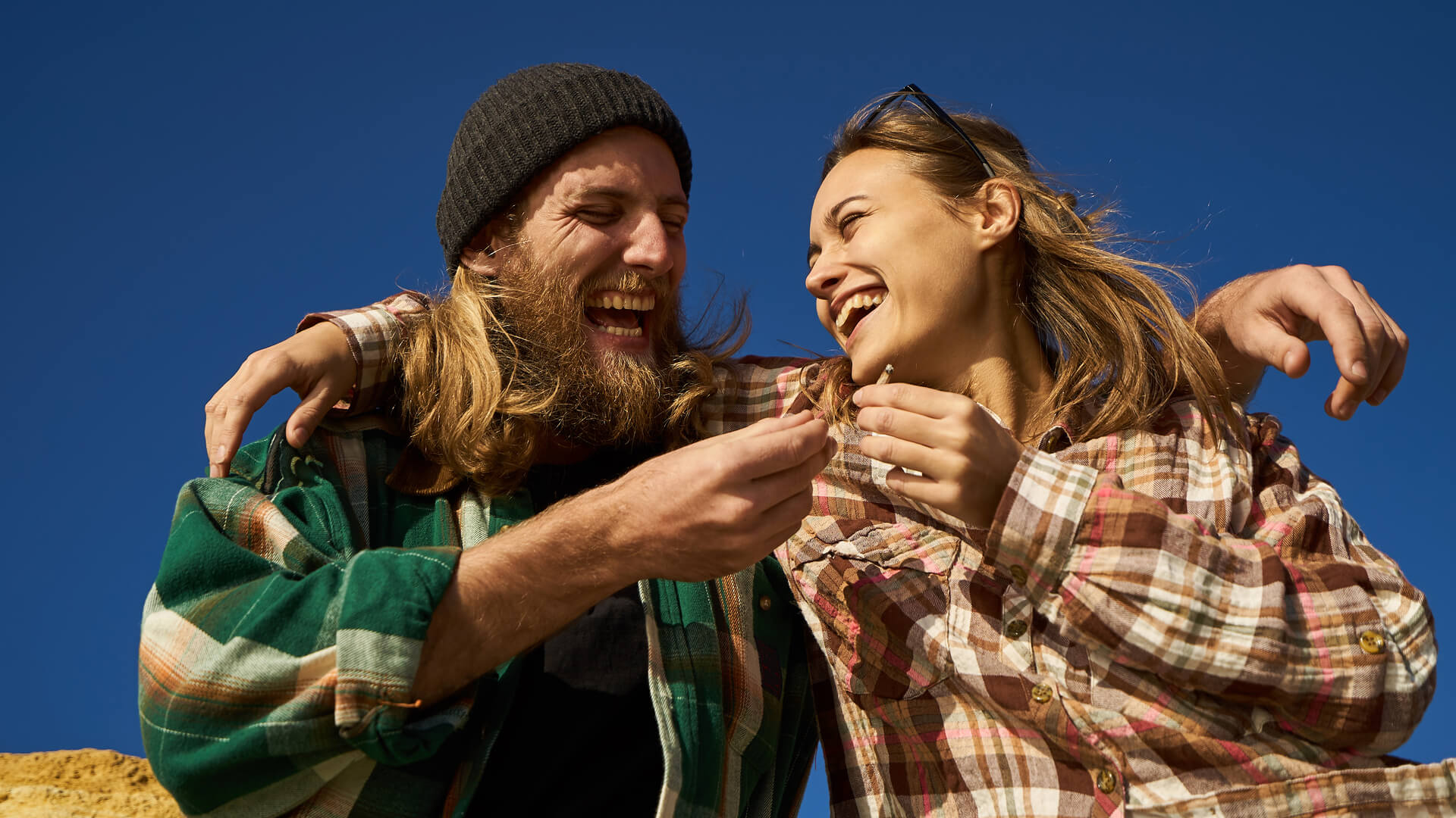 A hipster coupler laughing and passing a joint while hugging