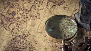 Magnifier with lantern and compass on an old map