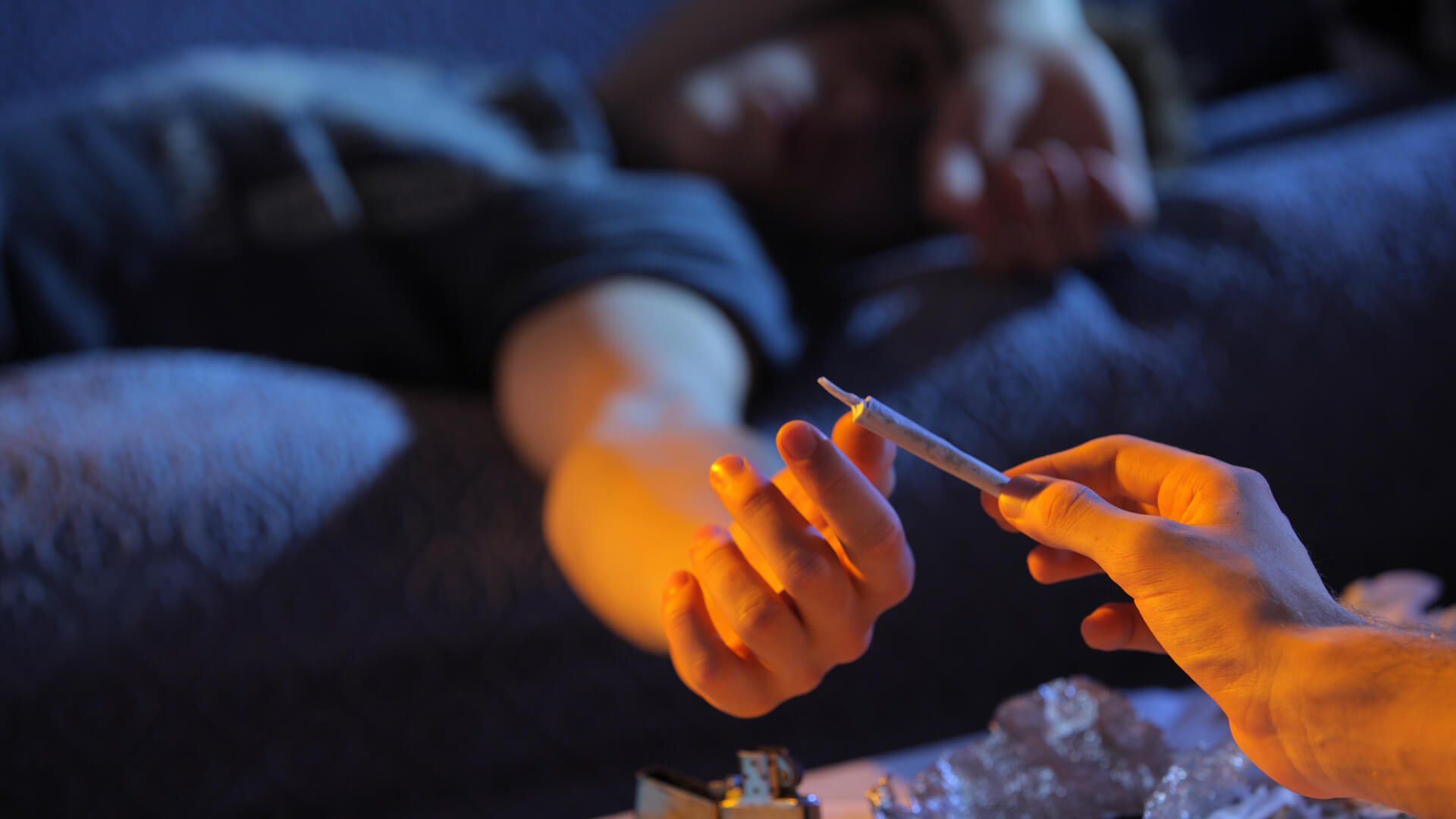 A young man passing a joint to his friend lying on the couch